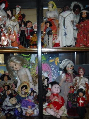 china cabinet full of antique dolls from around the world